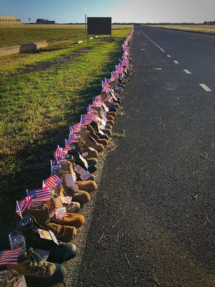 rows of military boots lining the roads of Ford Island with tags and pictures of those that have given their lives since 9/11